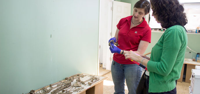Photo of Kimberlee Moran showing Julie Roncinske the lower jaw bone of an old woman excavated in the Arch street dig