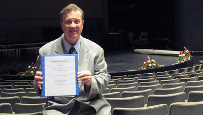 John Kendell holding the binder of his play in the Gordon Theater